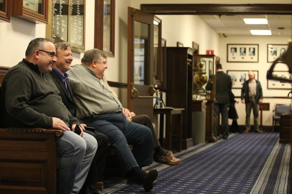Lobbyists Kris Knauss, left, Kevin Jardell and Ashley Reed sit on a second-floor bench at the state Capitol in Juneau on Friday, April 13, 2018. (Nathaniel Herz / ADN)