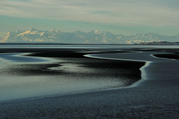 The glacial silt stretches off towards the mountains across Cook Inlet along the Seward Highway in Anchorage, Alaska, on Thursday, November 3, 2016. (Bob Hallinen / Alaska Dispatch News)