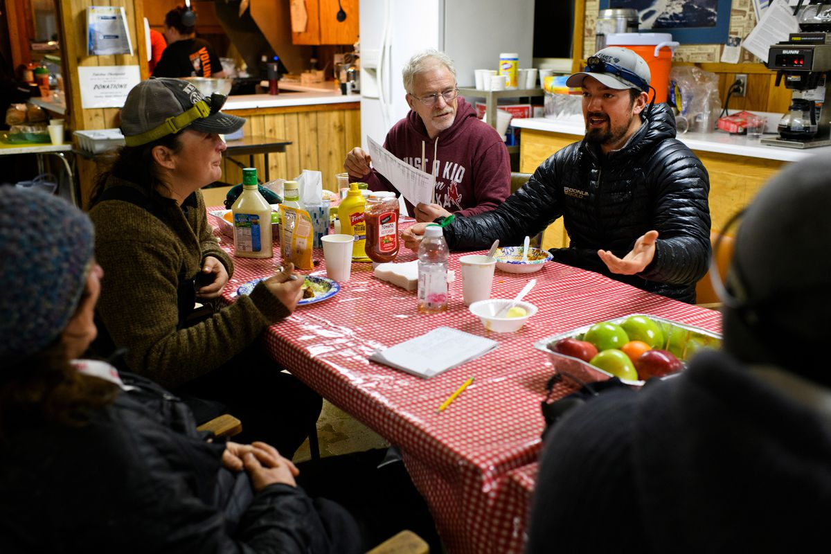 Mushers swap stories inside the Takotna community hall on March 6, 2019. From left are Michelle Phillips, Jessie Royer, Jeff King, Pete Kaiser and Richie Diehl. All but Phillips are racing in the 2019 Iditarod. (Marc Lester / ADN)