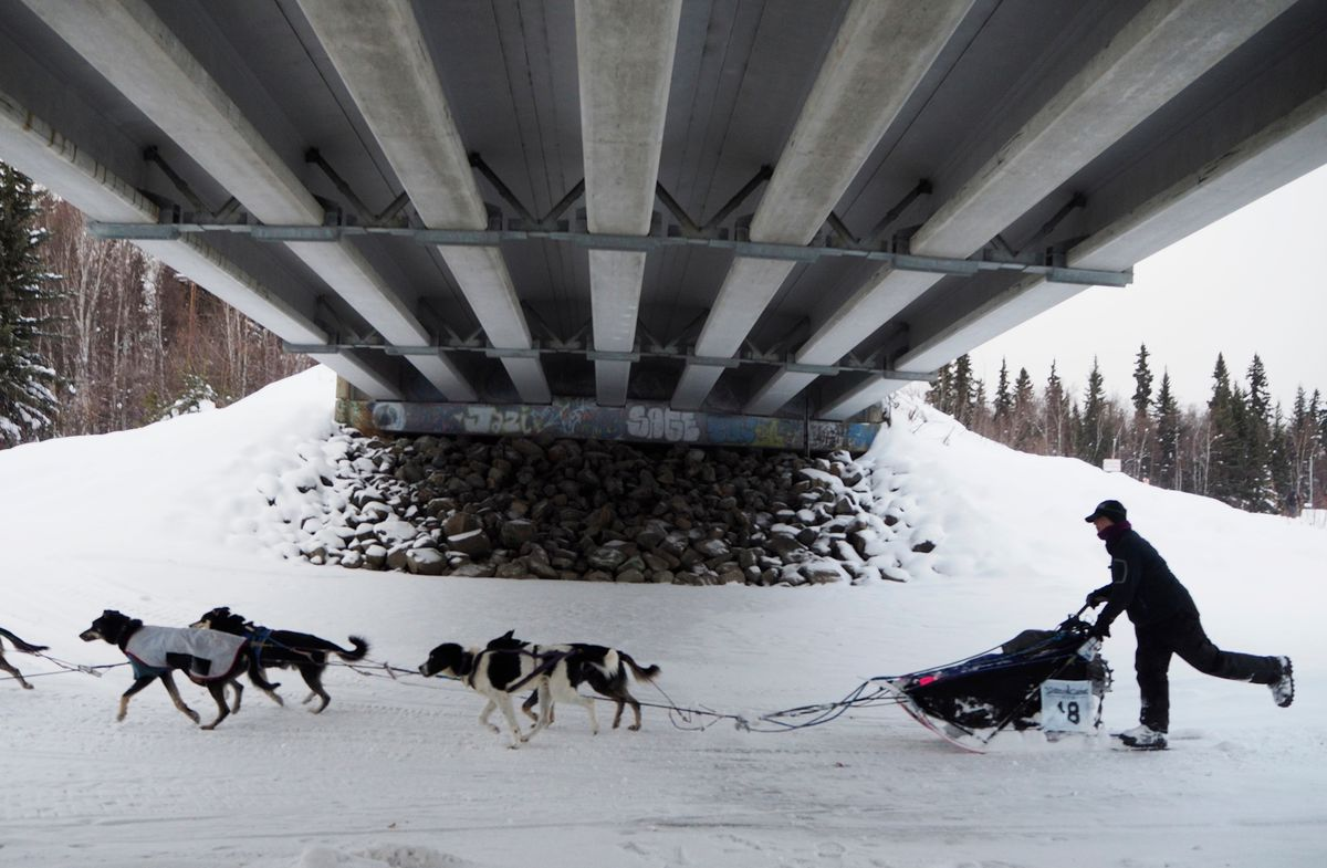 Jessie Royer passes under Nordale Road as she heads down the Chena River toward Fairbanks in the final hours of her Yukon Quest run on Tuesday afternoon. By Wednesday, this spot had become the finish line due to deteriorating ice downriver. (Marc Lester / ADN)