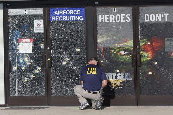 In this July 17, 2015 file photo, an FBI investigator investigates the scene of a shooting outside a military recruiting center in Chattanooga, Tenn. The deadly shootings of Marines at two Tennessee military sites illustrate the threat FBI officials in recent months have warned about: violence by a lone gunman with apparent terroristic aspirations against a vulnerable government target.
