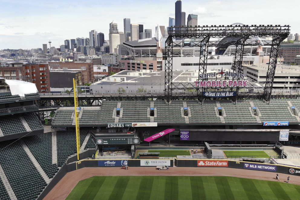 Downtown Seattle is seen beyond an otherwise empty Seattle Mariners' ballpark as baseball goes into its seventh week without play because of the coronavirus outbreak, Monday, May 11, 2020, in Seattle. (AP Photo/Elaine Thompson)