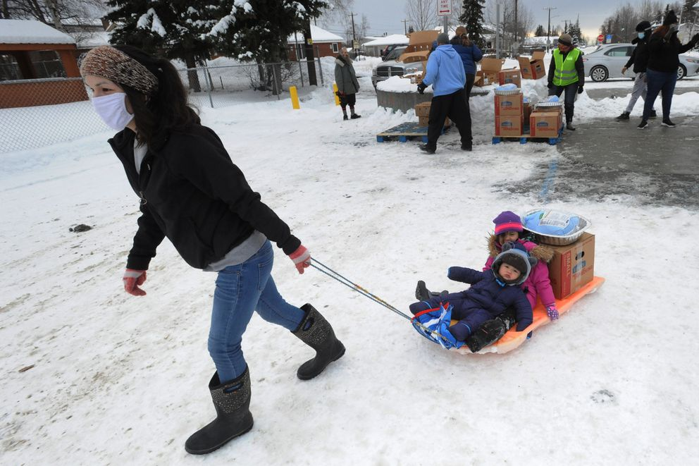 Tessie Hardiman-Agimuk pulls her children Oren Hardiman-Agimuk, 1, and Violette Gallegos, 4, in a sled after picking up a box of groceries and a frozen turkey during the annual Thanksgiving Blessing food distribution by the Food Bank of Alaska at the Mt. View Boys & Girls Club on Monday, Nov. 23, 2020. (Bill Roth / ADN)