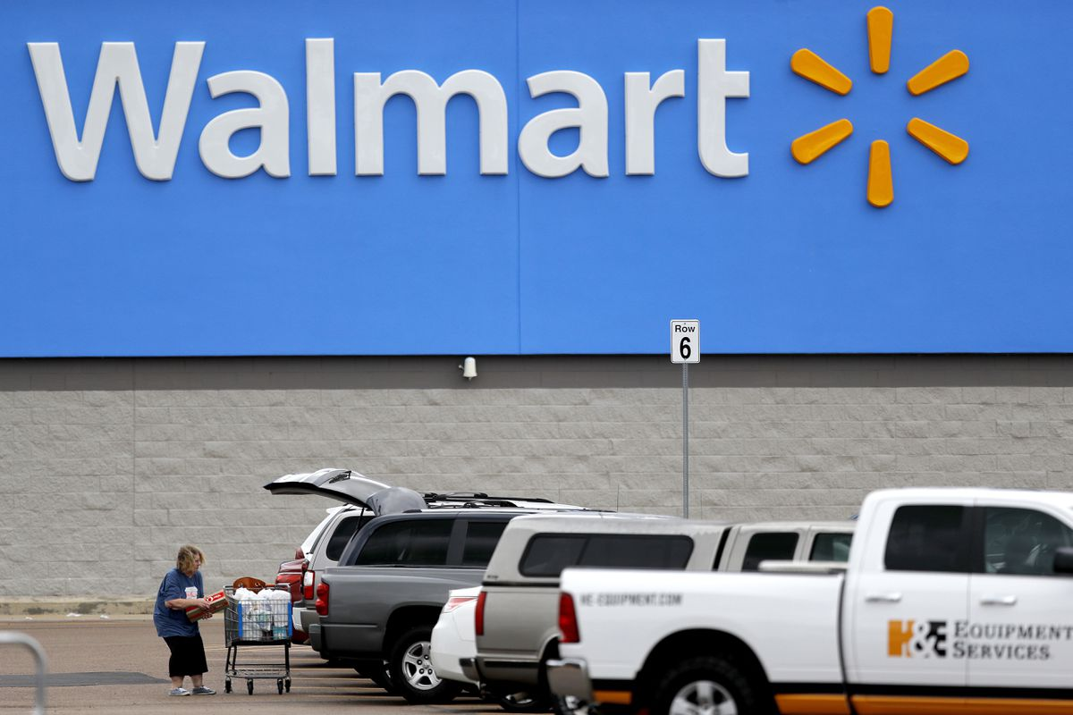 A woman pulls groceries from a cart to her vehicle outside of a Walmart store in Pearl, Miss. (AP Photo/Julio Cortez, File)