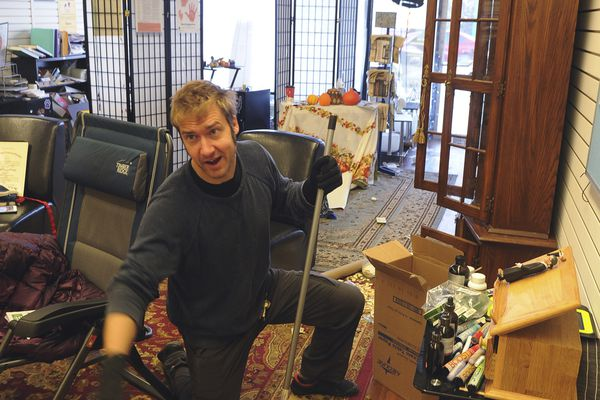 Tristan Covina helps clean up broken glass in the offices of the Institute Alaska, following an earthquake, Friday, Nov. 30, 2018, in Anchorage, Alaska. (AP Photo/Michael Dinneen)