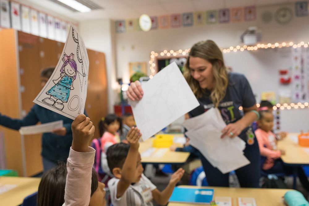 First grade teacher Allyson Small gathers artwork from her students on the first day of school Tuesday, Aug. 20, 2019 at Muldoon Elementary. (Loren Holmes / ADN)