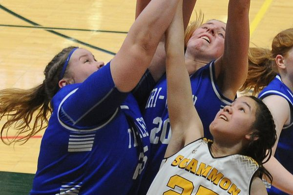 Olivia Juhl and Rachel Cockman, of Tri-Valley, and Adam Kaganak, of Scammon Bay, go up for a rebound in a quarterfinal game in the 1A girls Alaska State basketball tournament at the UAA Alaska Airlines Center in Anchorage, Alaska on Thursday, March 15, 2018. Scammon Bay defeated Tri-Valley 65-41. (Bob Hallinen / ADN)