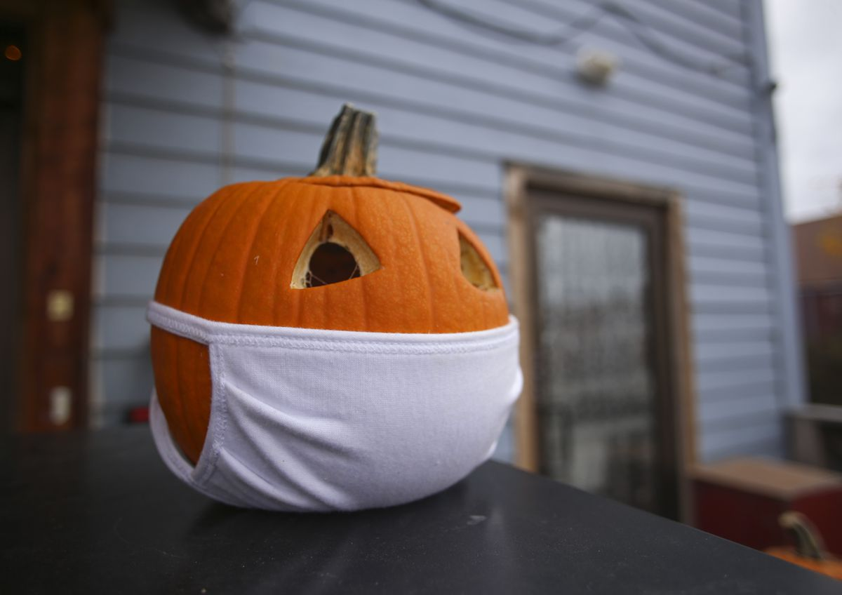 A pumpkin wearing a face mask is placed on the porch of Alaska Backpackers Inn on Eagle Street for decoration in Anchorage on Oct. 8, 2020. (Emily Mesner / ADN)