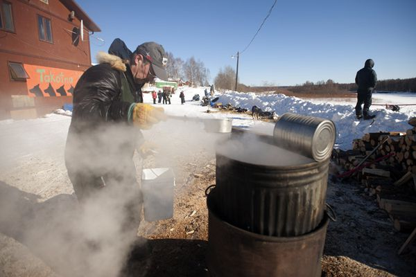 Rick Swenson gets hot water for his dogs at the Takotna checkpoint on Wednesday.
