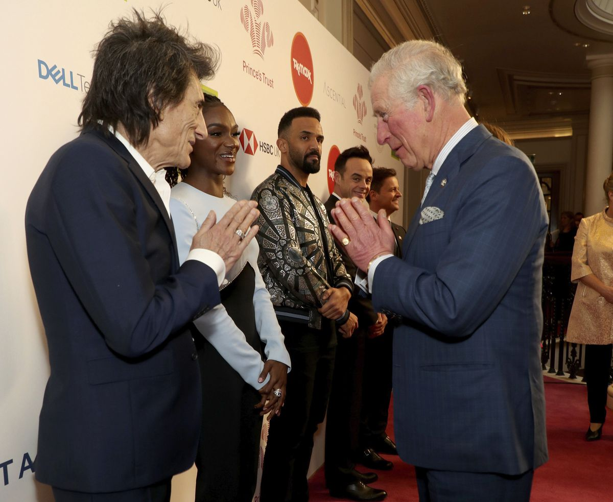 Britain's Prince Charles, gesture as he greets musician Ronnie Wood as he arrives at the annual Prince's Trust Awards 2020 held at the London Palladium, March 11, 2020. (Yui Mok/PA via AP, File)