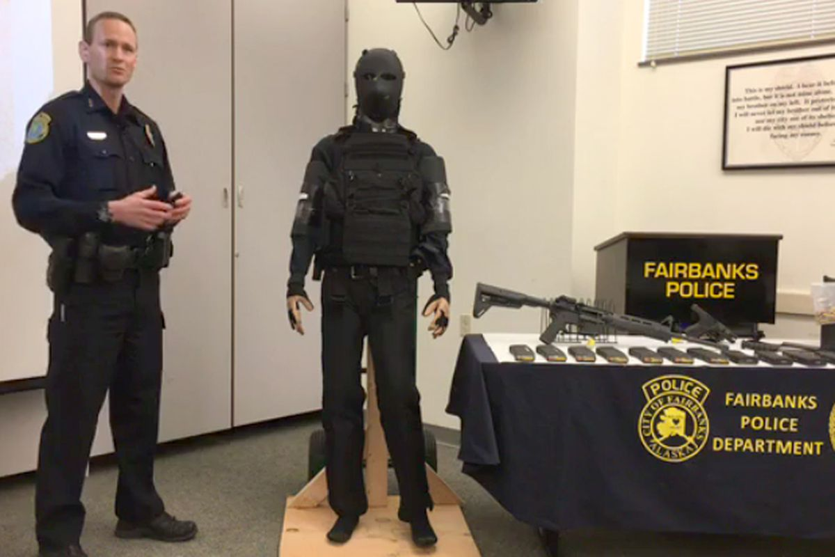 Fairbanks Police Department Chief Eric Jewkes stands next to the body armor worn by Matthew Stover, the 21-year-old who was shot and killed by police in June 2017. On the table is the fire arms and ammunition Stover had with him when he was killed. (Fairbanks Police Video screengrab)