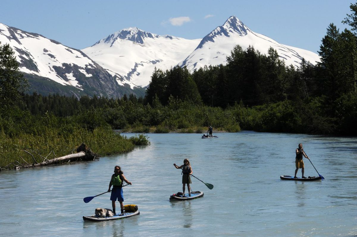 Karl Mittelstadt, left, leads a group of Girdwood residents as they negotiate Portage Creek on stand up paddle boards on a 70-degree day at the Portage Valley recreational area in the Chugach National Forest on Tuesday, June 21, 2016. (Bill Roth / Alaska Dispatch News)