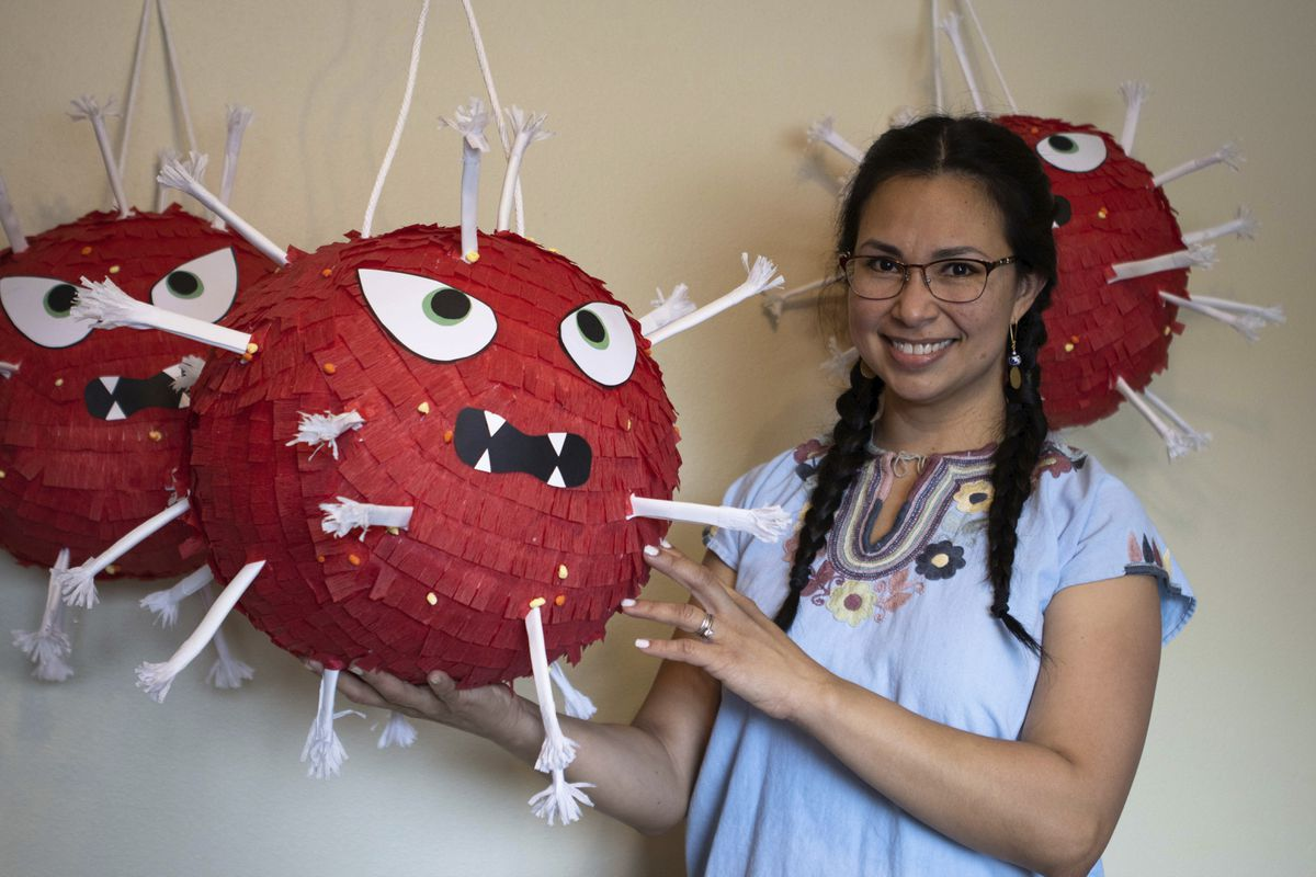 In this photo provided by Alaska Public Media, Carolina Tolladay Vidal displays custom COVID-19 piñatas in her home in Anchorage, Alaska, on April 14, 2021. After her business ground to almost a halt during the pandemic, she rejuvenated her business by making large, coronavirus shaped piñatas. (Hannah Lies/Alaska Public Media via AP)