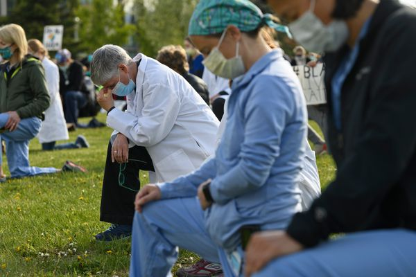 Demonstrators kneel for nine silent minutes. Healthcare workers gathered on the Delaney Park Strip for a quiet demonstration for racial equality on Saturday morning, June 6, 2020. (Marc Lester / ADN)
