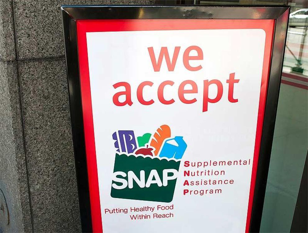 A sign indicates a store that accepts the Supplemental Nutritional Assistance Program or SNAP, the official name of the food stamp program. [File photo]