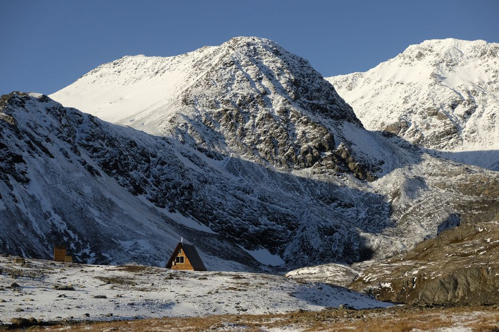 Snow gathers on the rugged mountains surrounding the Chugach National Forest cabin at Crow Pass in October 2014. (Marc Lester / ADN)
