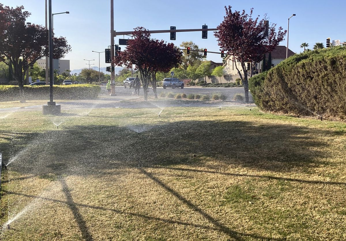Sprinklers water grass near a street corner Friday, April 9, 2021, in the Summerlin neighborhood of northwest Las Vegas. A desert city built on a reputation for excess wants to become a model for restraint with a first-in-the-nation policy limiting water use by banning grass that nobody walks on. Las Vegas area water officials are asking the state Legislature to pass a law banning