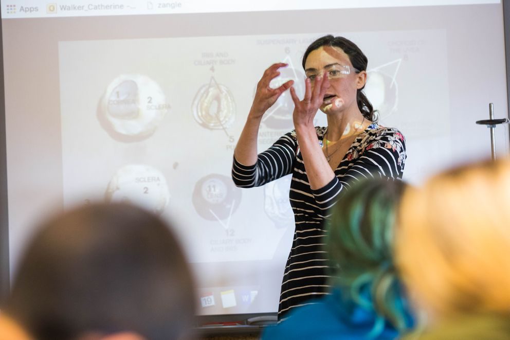 Walker, the award-winning Romig Middle School science teacher, works with seventh-graders to dissect a cow's eye. (Loren Holmes / Alaska Dispatch News)