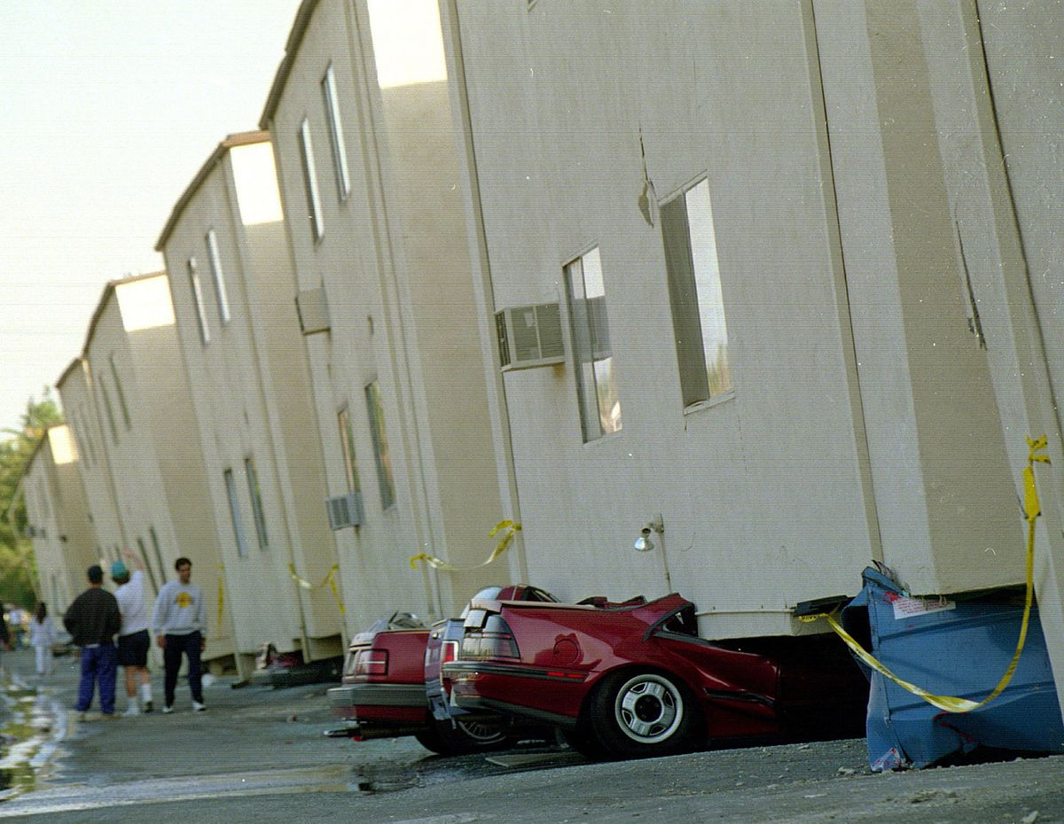 Autos sit underneath tilted aparment buildings in the 19100 block of Victory Boulevard in Los Angeles after the Northridge earthquake in January 1994. (Boris Yaro/Los Angeles Times/TNS)