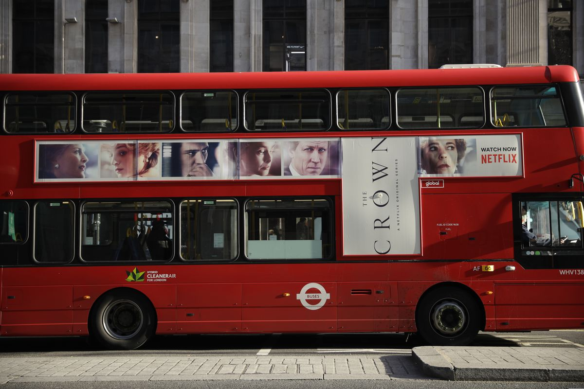 A traditional double decker red bus with an advert for