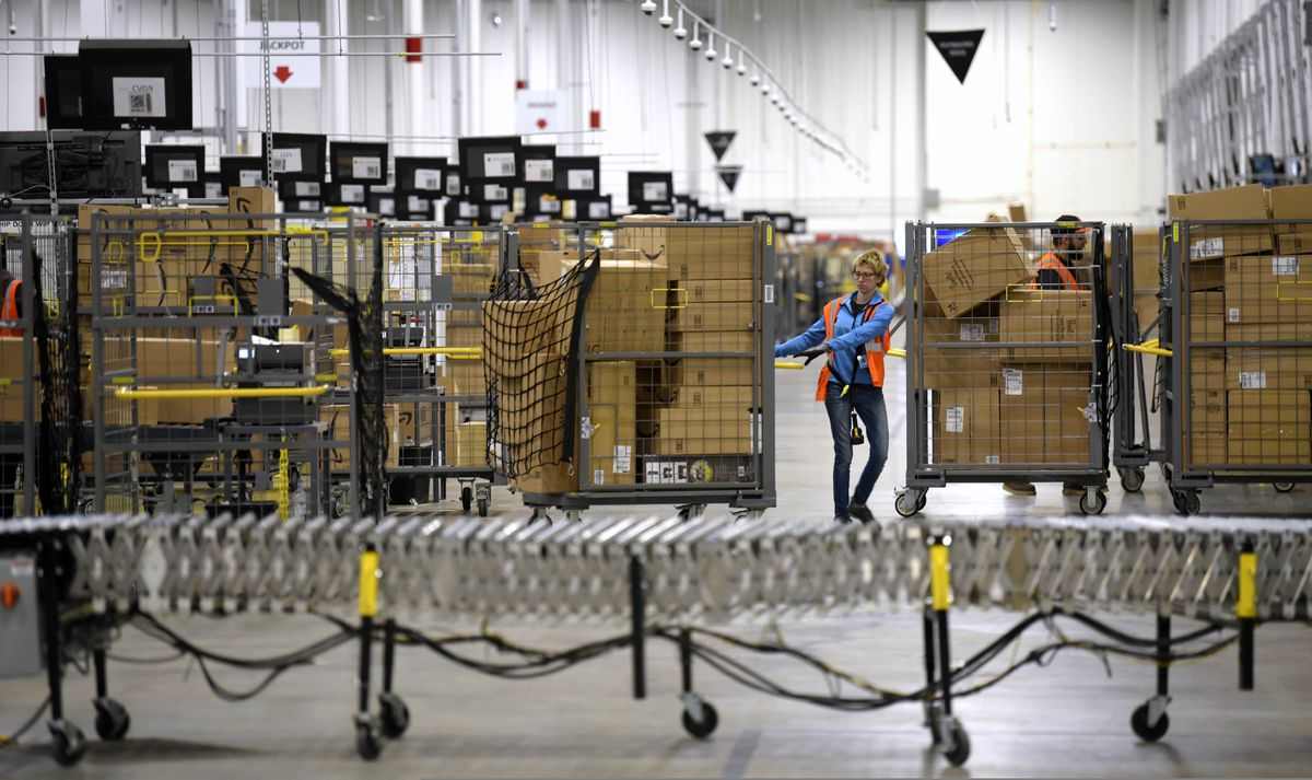 FILE - In this Friday, March 23, 2018, file photo, associates move bins filled with products at the loading dock of Amazon's then-new fulfillment center in Livonia, Mich. On Monday, March 16, 2020, Amazon said that it needs to hire 100,000 people across the U.S. to keep up with a crush of orders as the coronavirus spreads and keeps more people at home, shopping online. (Todd McInturf/Detroit News via AP, File)
