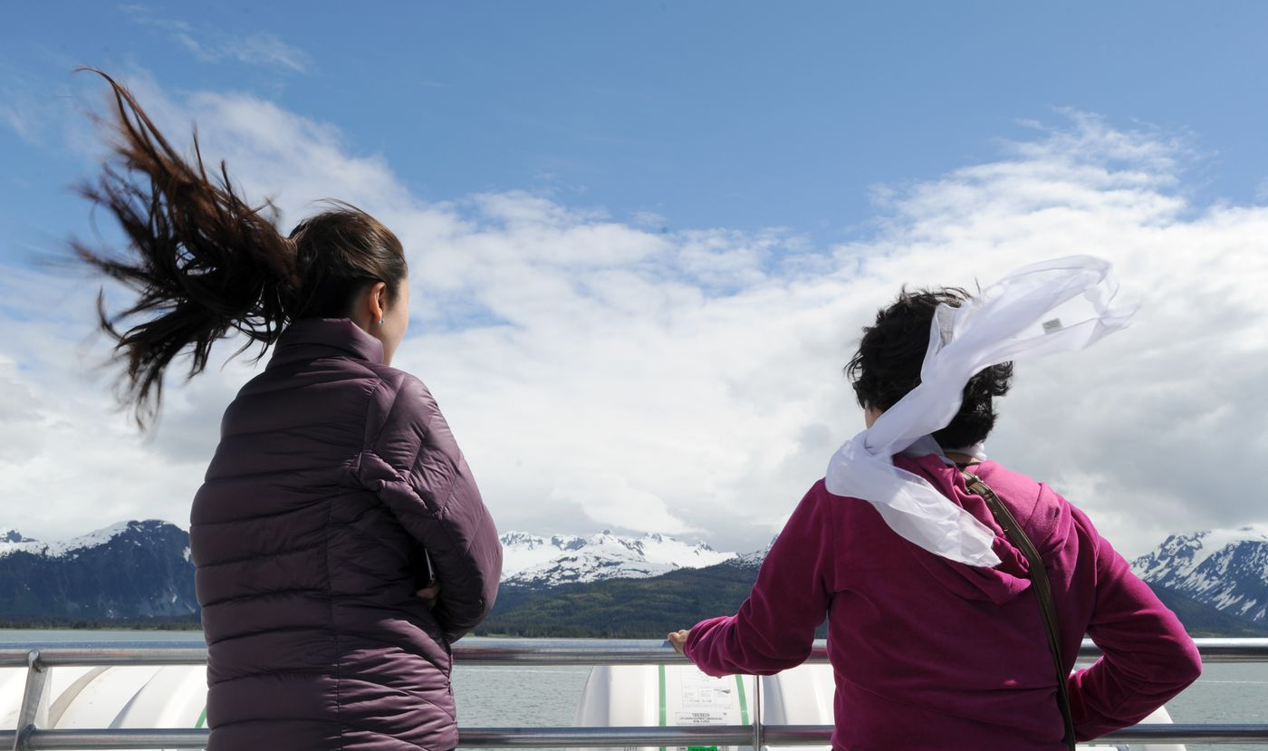 Vicky Tu's hair flies while Minghui Dong's scarf does the same in the wind aboard the Klondike Express in Prince William Sound. (Anne Raup / ADN)