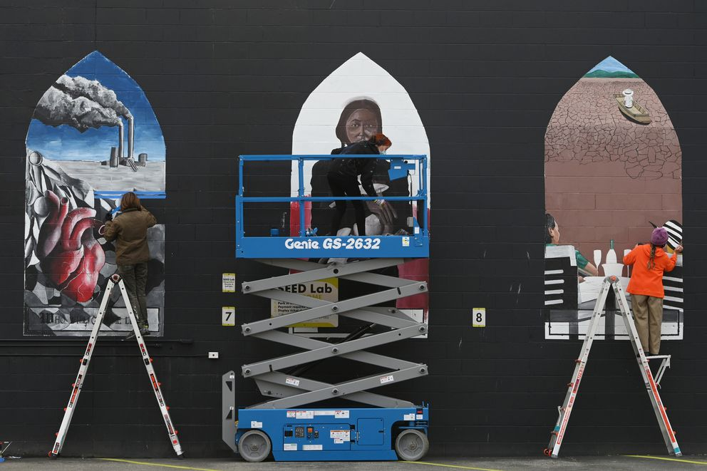 Local artists, from left, Noah Amason, Simone Bethancourt and Lina Villar, work on their contributions to a climate change mural being painted on the east side of the Anchorage Museum's SEED Lab in downtown Anchorage on Monday, Sept. 21, 2020. (Bill Roth / ADN)