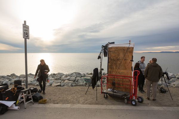 Celebrity portrait photographer Mark Seliger, in gray sweatshirt at right, breaks down his setup after photographing President Obama for Rolling Stone magazine on Shore Drive in Kotzebue on Wednesday.