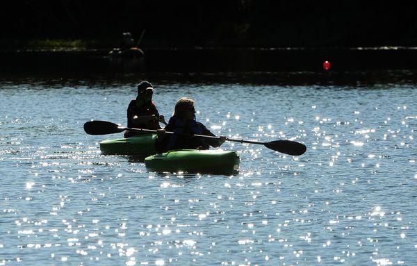 Wolfgang and Elaine Junge kayak across Little Campbell Lake on Saturday. (Bob Hallinen / ADN)