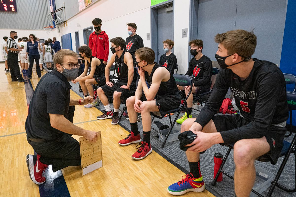 Houston High School JV basketball coach Jacob Byrley talks with his team before a game against the Redington High Huskies on Thursday, Feb. 11, 2021 at Redington High in Wasilla. The Matanuska-Susitna Borough School District began requiring masks for indoor activities this week after a number of schools shifted to remote learning due to COVID-19 outbreaks largely associated with unmasked sports and after-school functions. (Loren Holmes / ADN)