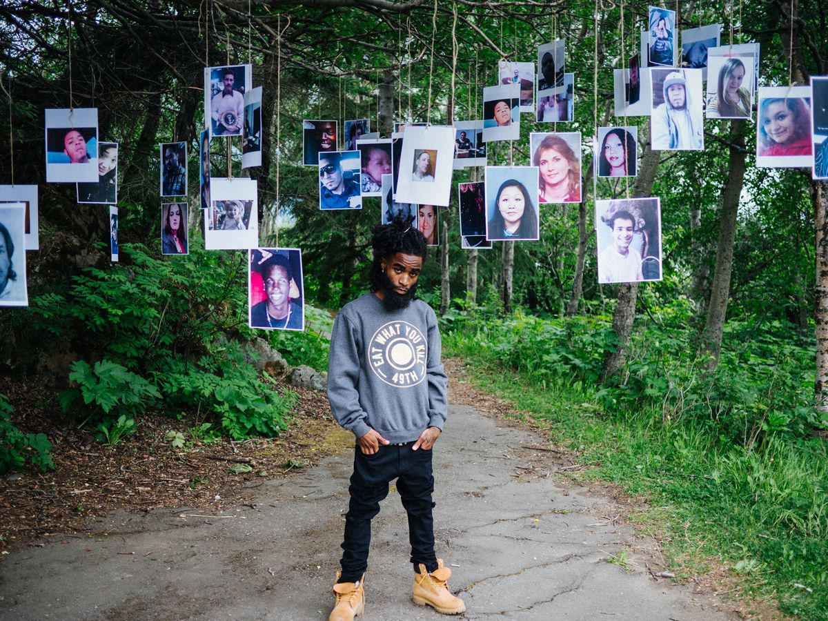"Anchorage hip-hop artist Tayy Tarantino surrounded by photos of Anchorage homicide victims, whom he pays tribute to on his new album, ""To Live and Die in AK."" (Photo by Bad Agenda)"