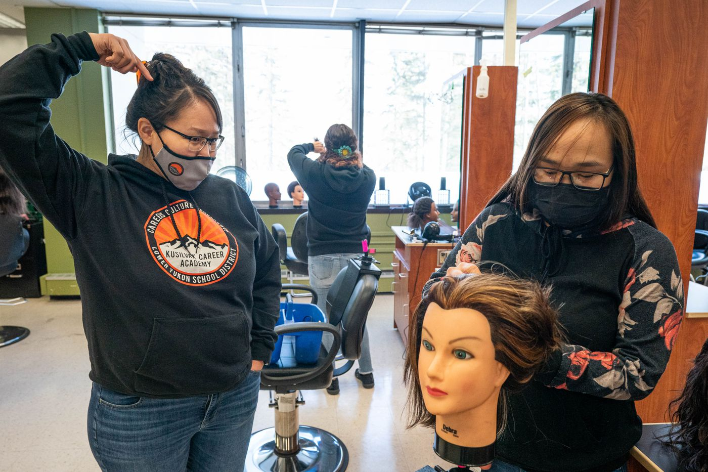 Amber Atchak, left, talks with Jeanette Paul during a cosmetology class at King Tech High School on April 2, 2021. Atchak is a resident assistant and instructional aide at Kusilvak Career Academy, where Paul is a student. Paul is from Pilot Station. (Loren Holmes / ADN)