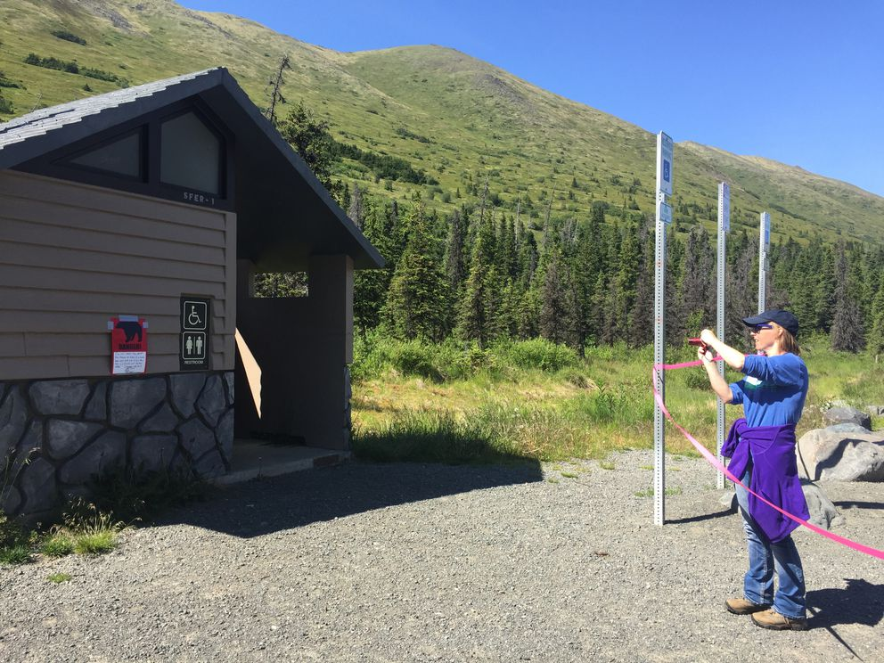 Kristen Pettit of Lisle, Illinois takes a photo of a closure sign at the South Fork Eagle River trailhead on Thursday. (Matt Tunseth/Alaska Star)