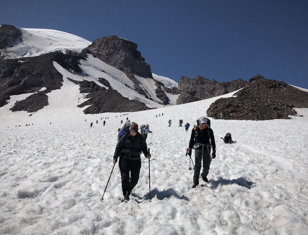 Rachel Ligtenberg, left, and Kazu Ishidera trek downhill in the snow from Camp Muir toward Paradise at Mount Rainier on July 16. At right in the background is Leah Koshiyama, who preferred a different method of descent. (Vicky Ho / Alaska Dispatch News)