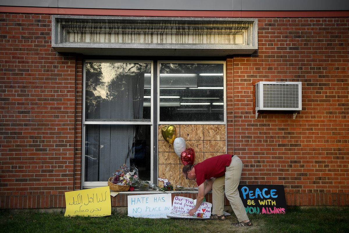 Ben Sunderlin places a sign of support near the window that was damaged during an attack at the Dar Al Farooq Islamic Center in Bloomington, Minn., on Tuesday, Aug. 8, 2017. Three Illinois men were arrested for the bombing. (Aaron Lavinsky/Minneapolis Star Tribune/TNS)