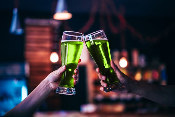 Two friends toasting with glasses of green beer. (Getty Images)