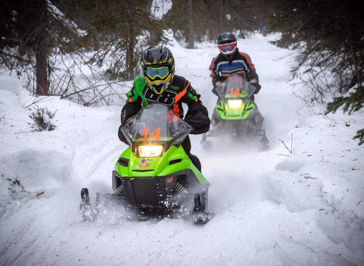 Jackson Carmichael and Devin Krause whip down the trail on their way to victory in the Scary Tree 50, a 50-mile snowmachine for racers under 18 held on the trails around Big Lake on Sunday, March 14, 2021. (Jesse Fliris / Alaska Shutterclicks)