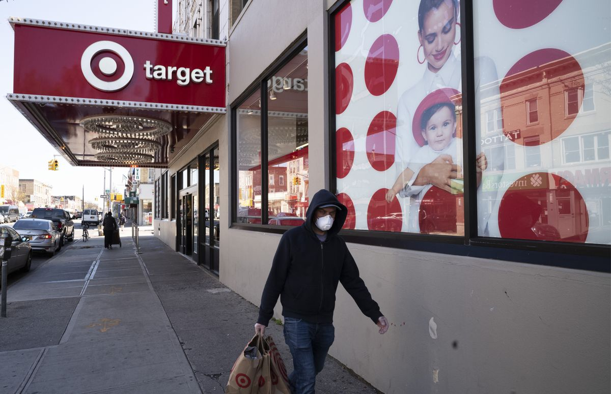 A customer wearing a mask carries his purchases as he leaves a Target store during the coronavirus pandemic in the Brooklyn borough of New York. Target has joined a growing list of major retailers that will require customers at all their stores to wear face coverings. (AP Photo/Mark Lennihan, File)