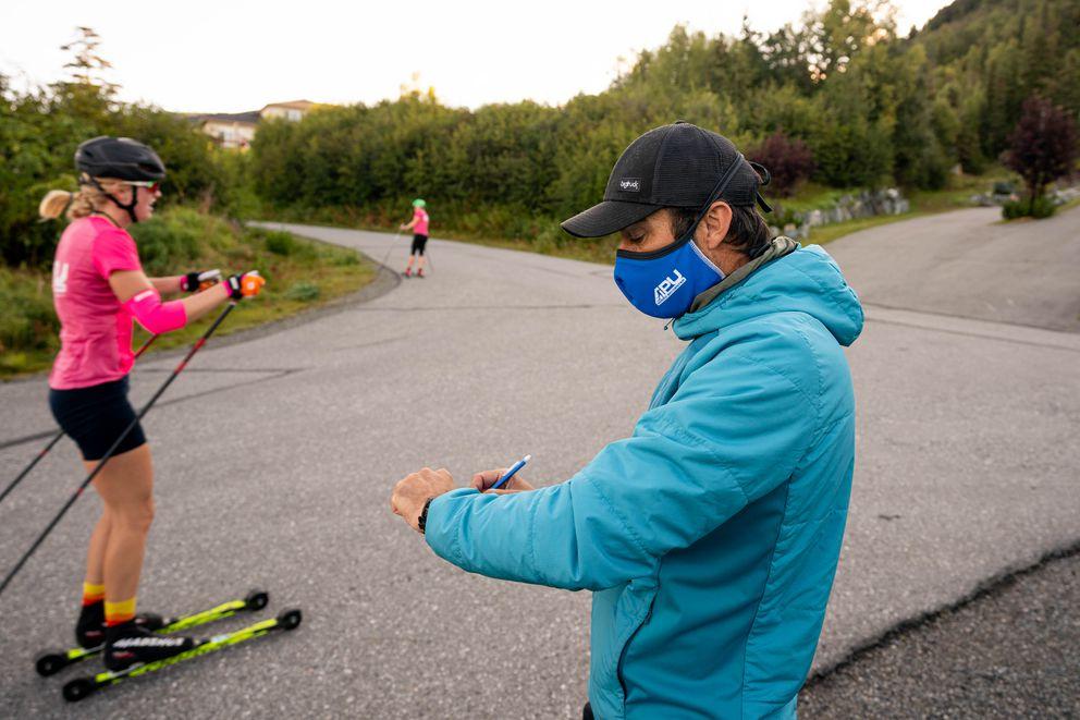 Alaska Pacific University coach Erik Flora records times at the finish. (Loren Holmes / ADN)
