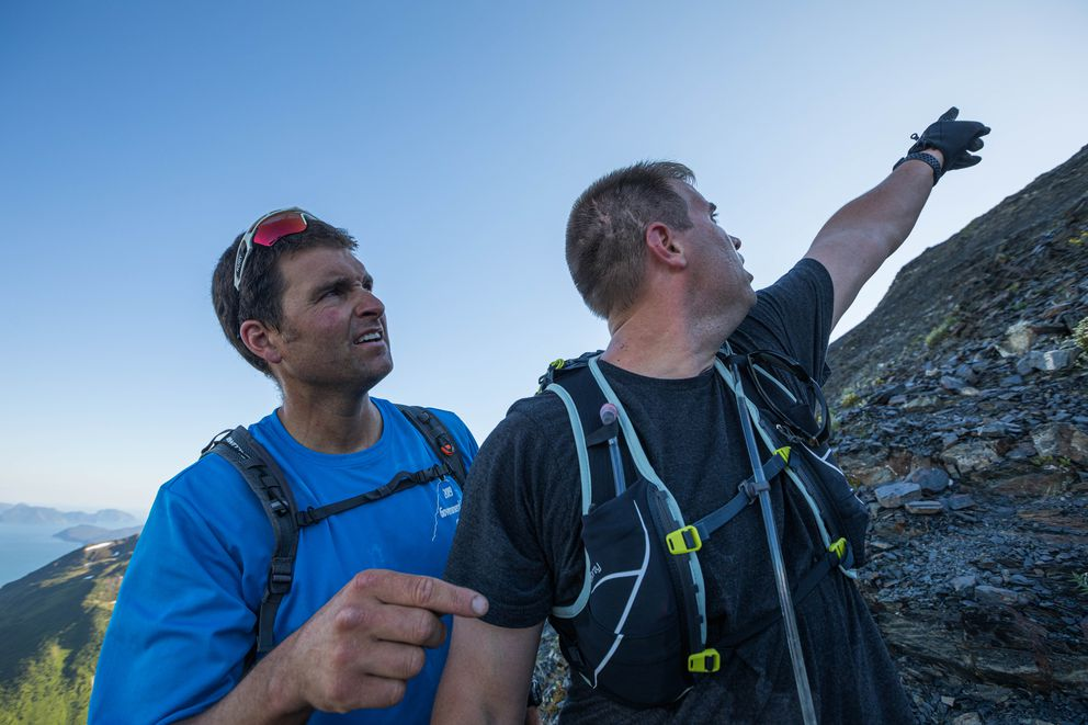 Veteran racer Rob Whitney, left, and Ben Schultz look at the trail on the Mt. Marathon race course Wednesday. Whitney, a veteran mountain runner, was helping Schultz become familiar with the steep, technical trail. (Loren Holmes / ADN)
