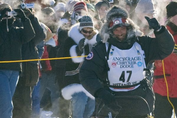 Lance Mackey pumps his fist as he heads down Front Street in Nome to claim victory in the 2009 Iditarod on March 19, 2009. (Marc Lester / Anchorage Daily News)