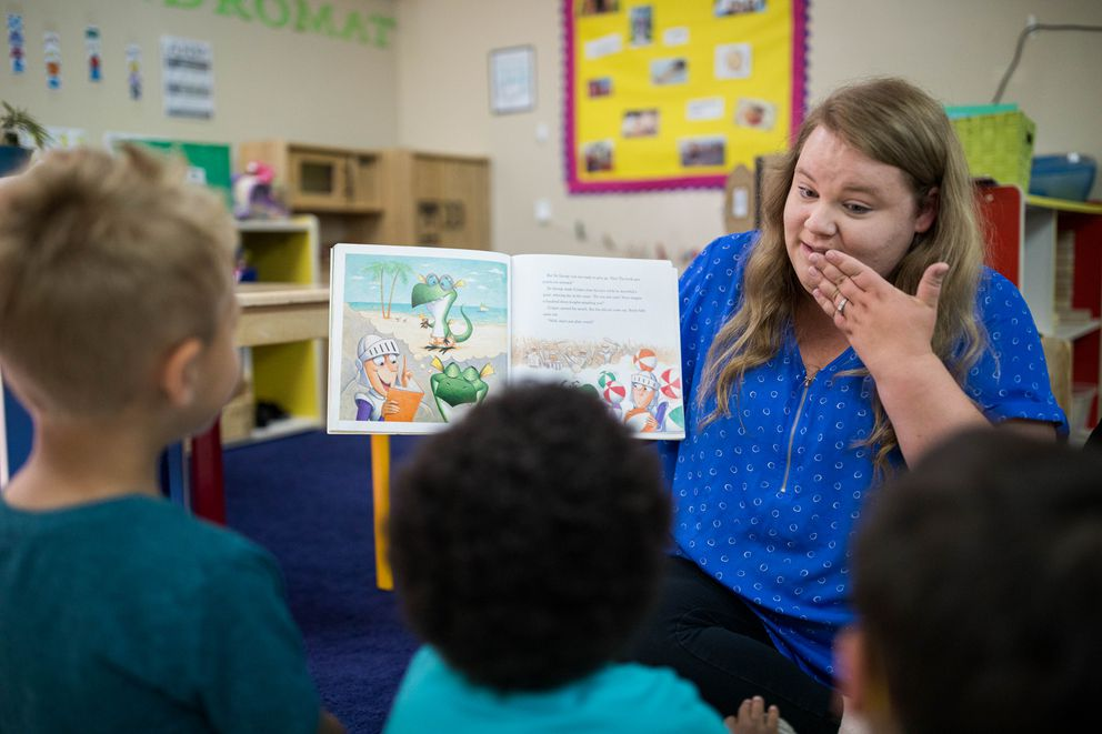 Kayla Reed, a teacher at a Kids' Corps Inc. pre-K program, reads to children Tuesday, July 9, 2019 in Anchorage. (Loren Holmes / ADN)