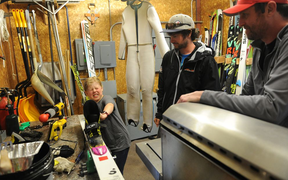 Zak Hammill watches a jumper try out the binding on one of her skis at the 2018 Midnight Sun Ski Jump-a-thon. (Bob Hallinen / ADN archive)