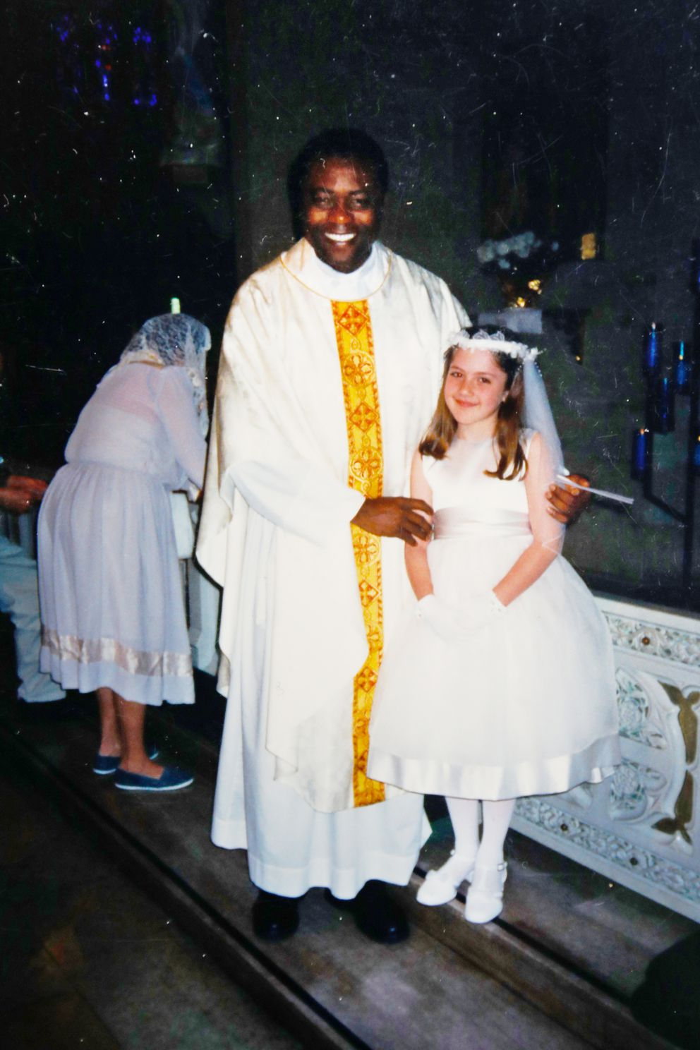 This undated photo provided by Mary Rose Maher in 2019 shows her as a child standing with Rev. Komlan Dem Houndjame at The Assumption of the Blessed Virgin Mary Church in Detroit. Two years after arriving at The Assumption of the Blessed Virgin Mary Church in 1999, Detroit Archdiocese officials said they asked Houndjame to return to his home country, Togo, after learning of accusations of sexual misconduct against him in Detroit and at an earlier posting in Florida. Instead he went to a treatment facility in St. Louis. In 2002, Detroit police arrested him and charged him with sexually assaulting a member of the church's choir. (Courtesy Mary Rose Maher via AP)