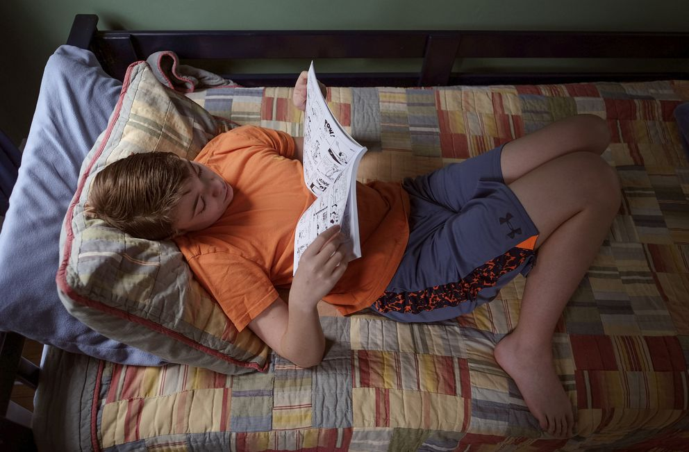 Jackson Leyden reads in his bedroom. (Bonnie Jo Mount / The Washington Post)