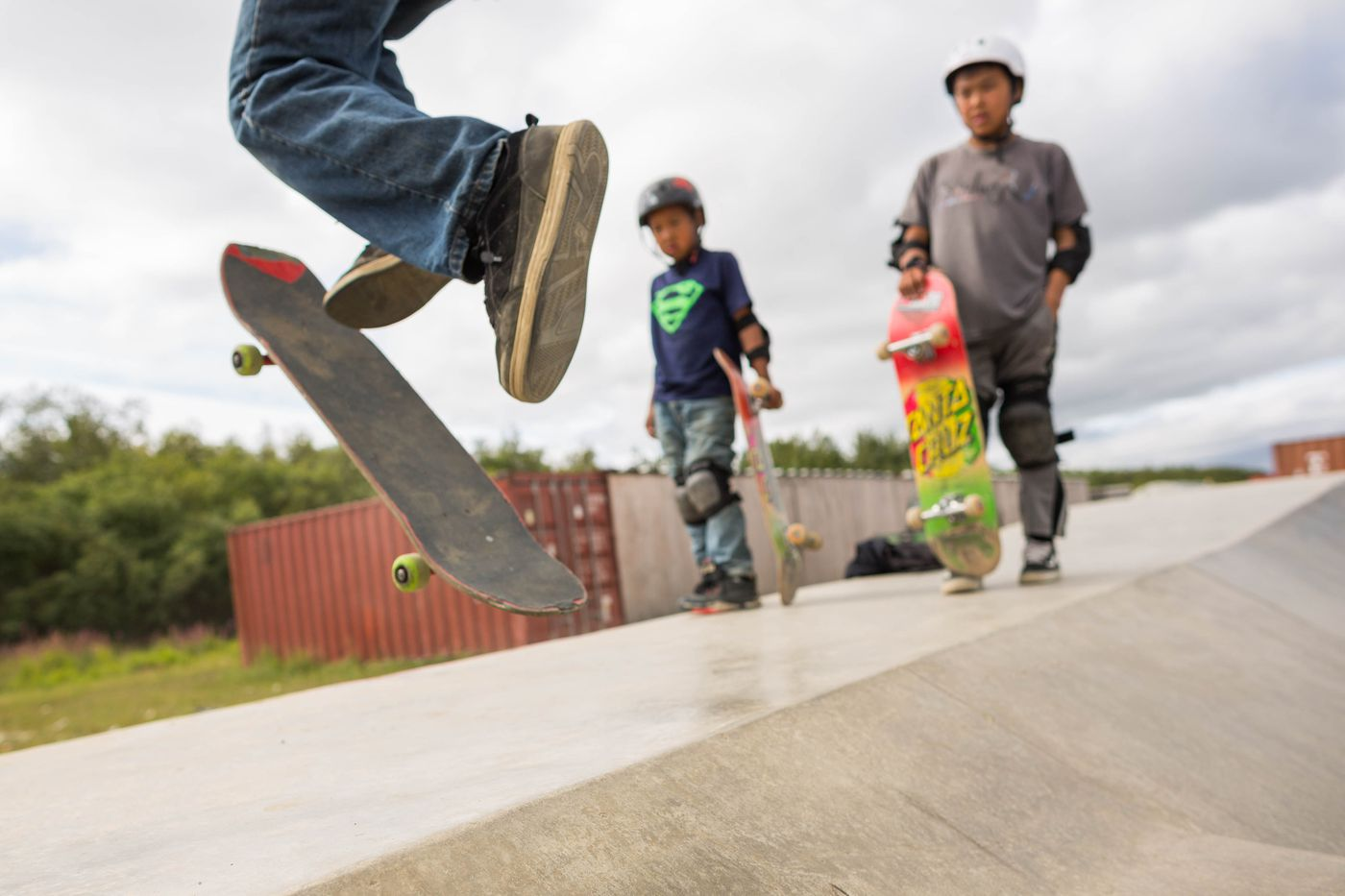 Ian Fischer, 9, left, and Evan Waska, 13, watch Ethan Nicolai, 13, practice a trick at the Kwethluk skate park on Friday, August 7, 2015. The park, which was built with an Indian Health Services grant, is the only one of its kind in a small rural Alaska village. (Loren Holmes / ADN)