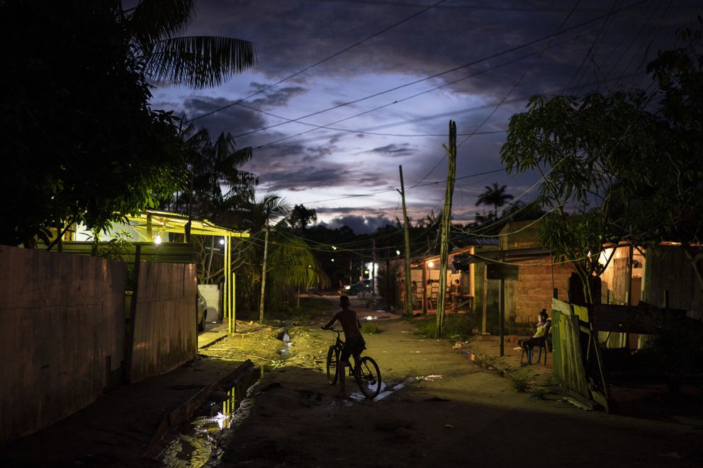 A boy rides his bike at dusk through the Park of Indigenous Nations community, where many residents have fallen ill with symptoms of the new coronavirus, in Manaus, Brazil, Sunday, May 10, 2020. Per capita, Manaus is Brazil's major city hardest hit by COVID-19. (AP Photo/Felipe Dana)