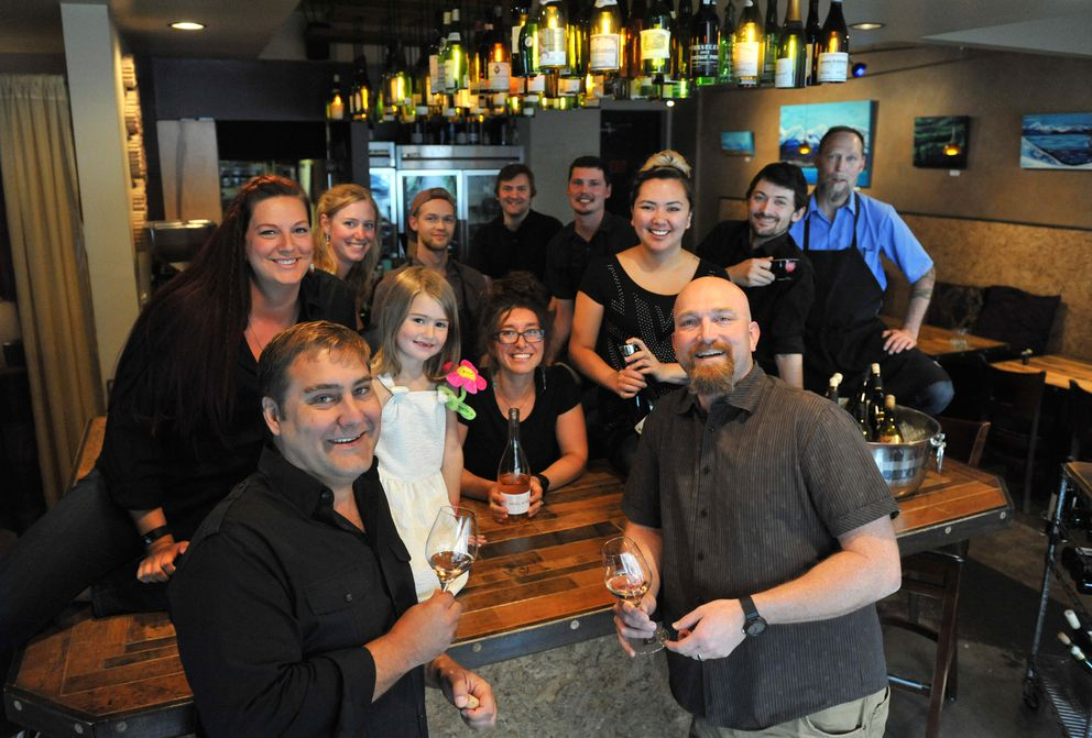 Crush Wine Bistro and Cellar owners Scott Anaya and Robert DeLucia, Anaya's daughter Cooper Carranaya, and the rest of the bistro staff gather around the bar on Friday. (Bob Hallinen / Alaska Dispatch News)