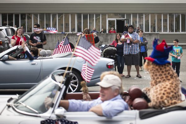 People line the sidewalk to watch the Fourth of July parade on Tuesday as classic cars roll by the Delaney Park Strip in Anchorage. (Rugile Kaladyte / Alaska Dispatch News)