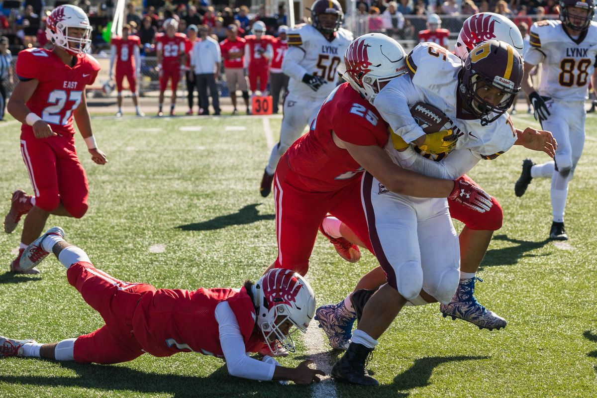 Dimond's Gio Young is tackled by East's Bladen Stubbs on Saturday at East High. East won 47-0. (Loren Holmes / ADN)